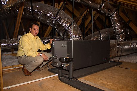 ClimateMaster Builder Development Manager Titian Burris kneels beside a ClimateMaster Geothermal Heat Pump in a home attic in Somer's Pointe.