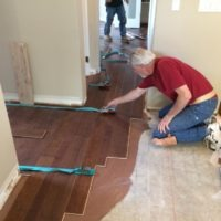 men working on hardwood flooring of home