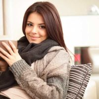 brunette haired woman sipping coffee on couch