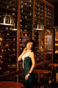 A woman in front of the wine cellar